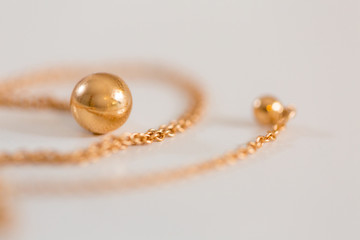 18K golden ball necklace isolated on white closeup