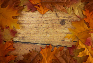 Fall Border of Red and Orange Leaves on a Wooden Background