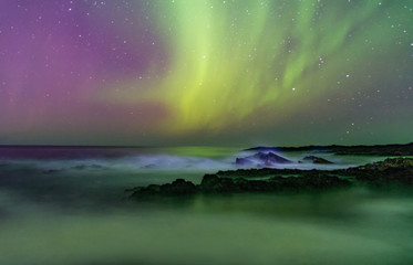 The starry sky and the northern lights above the ocean. Milk waves. Long exposure.