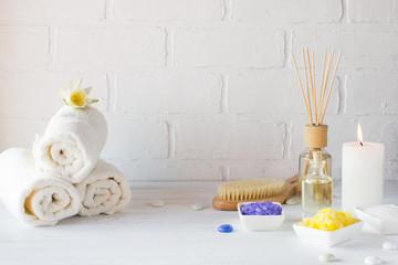 Spa still life with towel,white lily, sea salt, bath oil, sugar body scrub and candle
