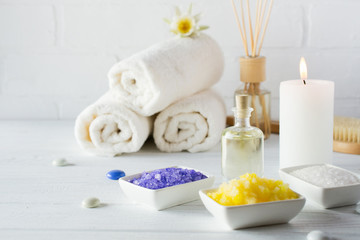 Spa still life with towel,white lily, sea salt, bath oil, sugar body scrub, massage brush and candle