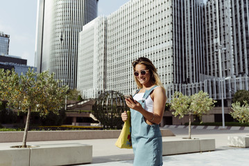 Smiling woman with smartphone on street