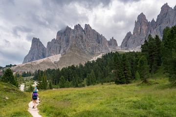 Hikers on Santa Magdalena St Maddalena Val di Funes in Dolomites Italian Alps with Furchetta mountain peak