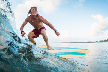 Young surfer rides ocean tropical wave