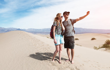 Couple of hikers takes selfie picture being on the sandy desert. The Death Valley, USA.