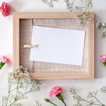 A wooden mockup frame surrounded by white and pink flowers