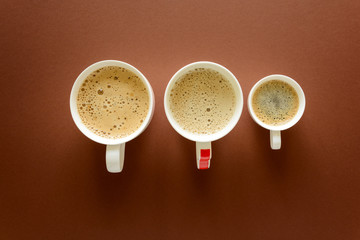 Different types of coffee. Late, cappuccino and espresso on brown background. Top view. Flat lay.
