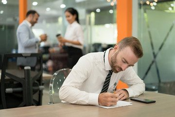 Focused young business man making notes and working at desk in office. Two colleagues relaxing and standing in background. Manager occupation concept.