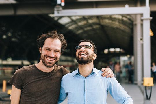Deutscher Mann und syrischer Mann lachen gemeinsam