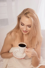 Young woman sitting in bed looking in a cup of coffie