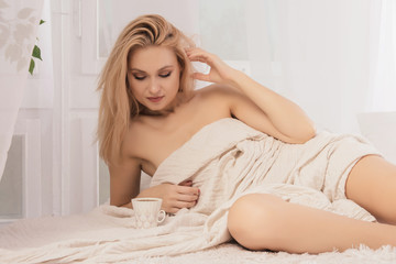 Young woman lies in bed with a cup of coffie