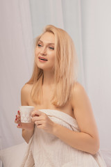 Young woman sitting in bed with a cup of milk, looking away