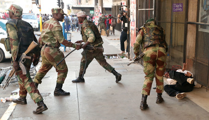 Soldiers beat a supporter of the opposition Movement for Democratic Change party of Nelson Chamisa outside the party's headquarters as they await results of general elections in Harare
