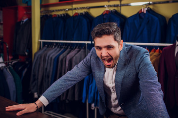 Tailor, tailoring. Men's suit, tailor in his workshop. Elegant man's suits hanging in row. Luxury mens classic suits on rack in elegant men's boutique. yawns tired choosing