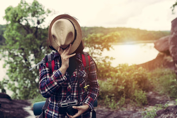 Hipster style women backpacker traveller standing hat off