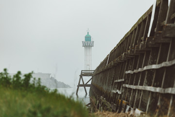 Pier and lighthouse in the harbour of Deauville on a misty morning in Normandy, France. English channel seascape