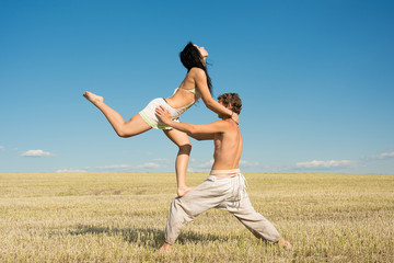 Young guy and girl doing acrobatic stunts against a clear blue sky. Sport. Healthy lifestyle.