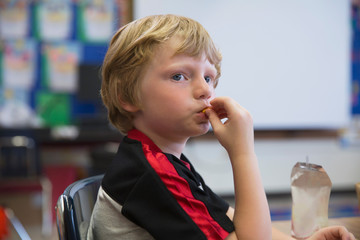 A student having a snack in a kindergarten classroom.