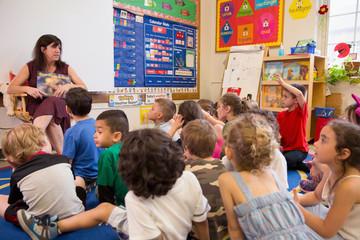 Students listening to their teacher in a kindergarten classroom.