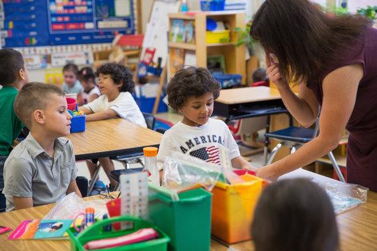 A teacher helping her students in a kindergarten classroom.