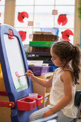 A student painting in a kindergarten classroom.