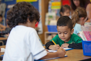 A child writing in a kindergarten classroom.