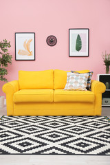 Modern living room interior with comfortable yellow sofa near color wall
