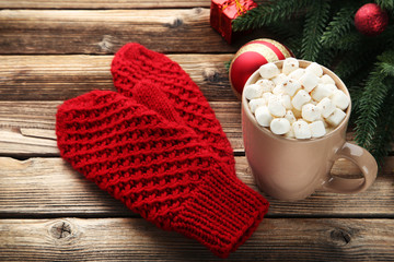 Knitted red gloves with cup of coffee and fir-tree branches on wooden table