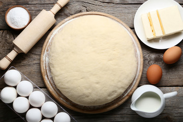 Raw dough with butter in plate and eggs on wooden table