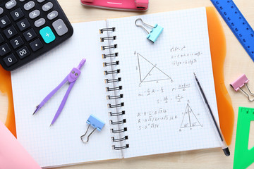 Exercise book with maths formulas and school supplies