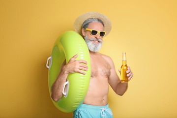 Shirtless man with inflatable ring and bottle of drink on color background