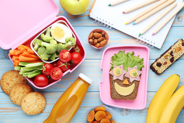 School lunch box with vegetables and fruits on blue wooden table