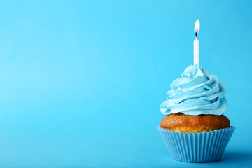 Tasty cupcake with candle on blue background