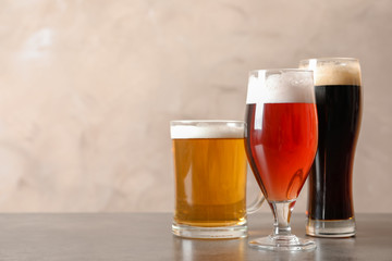 Glasses with different types of cold tasty beer on table