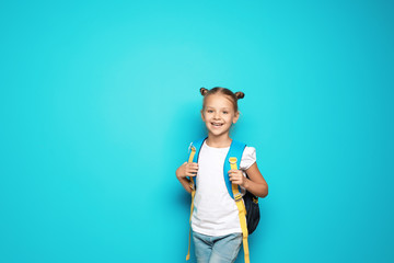 Little school child with backpack on color background