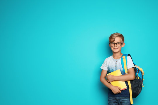 Little school child with backpack and copybooks on color background
