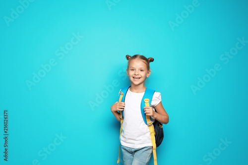 d3a26b4129 Little school child with backpack on color background