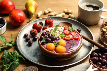 Bowl of tasty acai smoothie and ingredients on wooden table
