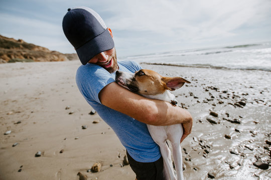 Man playing with dog at ocean beach