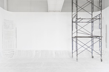 Construction and abstract background. White room renovating work process with white painted on wall and floor with scaffolding. Picture for add text message. Backdrop for design art work.