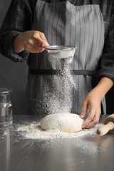 Woman sprinkling dough for pastry with flour on table