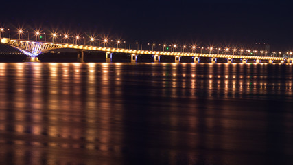 Song exposure shot of the brigde above Volga river with beautyfull lights reflected at water