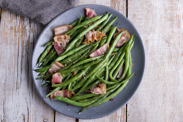 green roast beans with bacon on a plate