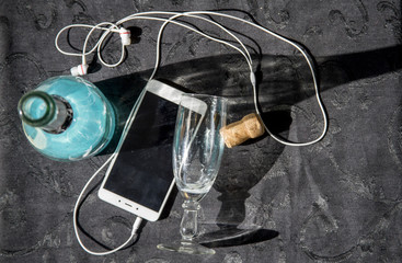 White smartphone with white headphones, bottle with blue drink and empty glass on a blue tablecloth, flat-lay