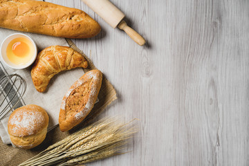 fresh bread and wheat on sack and wooden table.