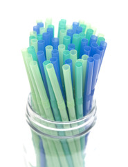 Bunch of Straws in a Glass Container on a White Background
