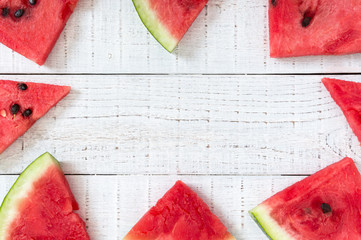 Juicy slices of a ripe watermelon on a white wooden background. Berry food background. Top view.  Flat lay. Free space for your project.