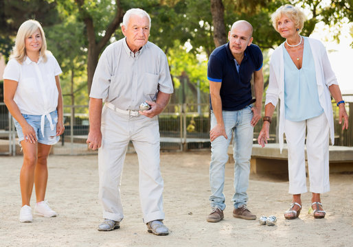 Positive mature people friends playing petanque in park