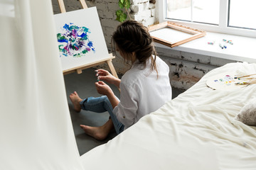 Back view of beautiful brunette girl in white shirt and jeans, sitting at work place and creating, drawing picture with oil colorful paints. Pretty woman, female artist holding brush and palette.