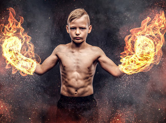 Young shirtless boy boxer wearing burning boxing gloves posing on the dark textured background.